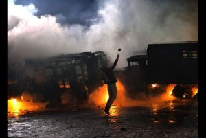 With support from the Government of Stephen Harper, Ukrainian protesters burn buses in Kiev. Source.